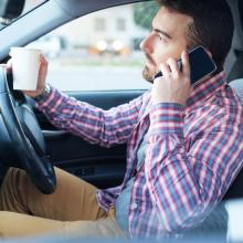 Driver on phone with coffee cup